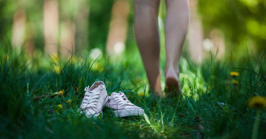 Persona descalza caminando en pasto