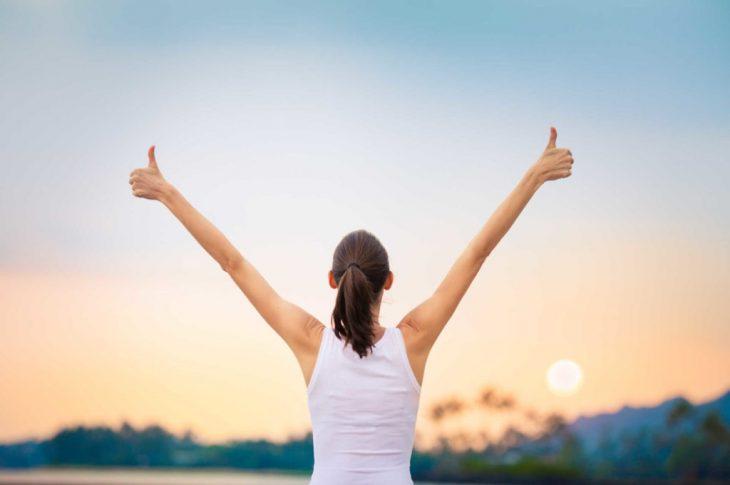 Mujer con playera blanca levantando las manos ante el atardecer