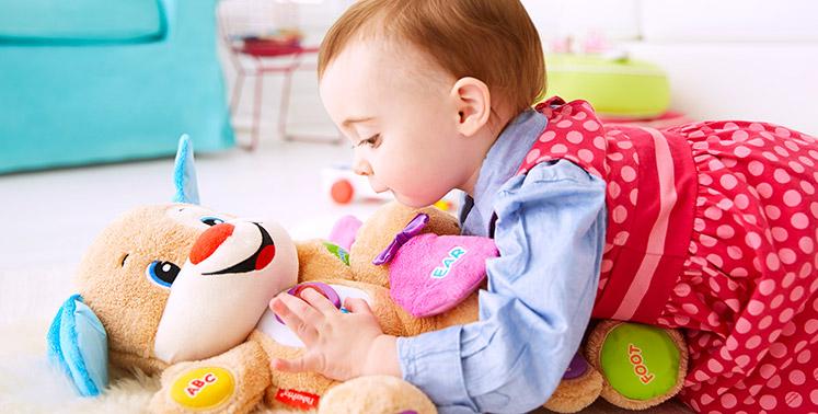 Niña jugando con su peluche en el piso de la sala