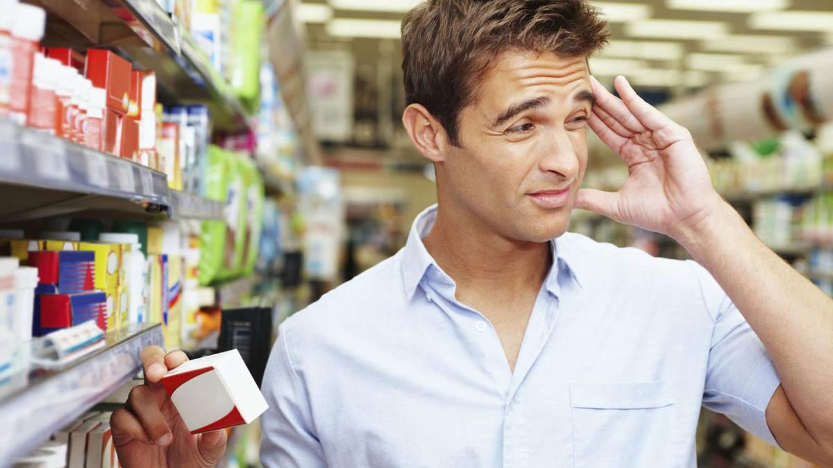 Hombre con migraña comprando medicamentos aurax genéricos.